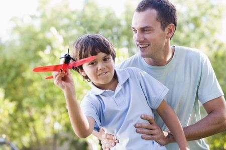 Man and young boy outdoors playing with toy airplane smiling photo