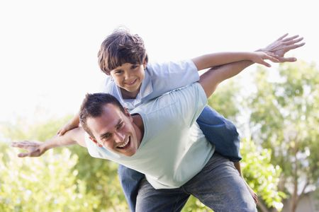 back yard: Man and young boy outdoors playing airplane smiling