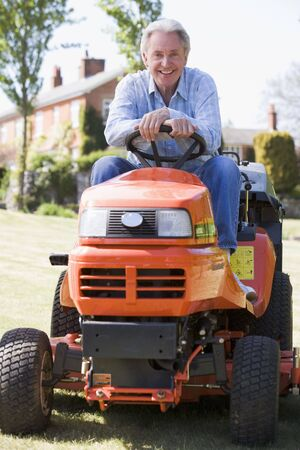 Man outdoors on lawnmower smiling photo
