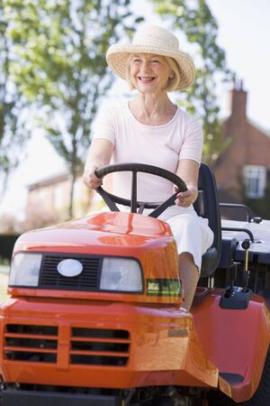 Woman outdoors driving lawnmower smiling photo