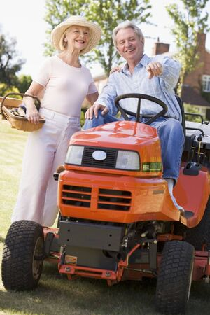 Couple outdoors with tools and lawnmower pointing and smiling photo