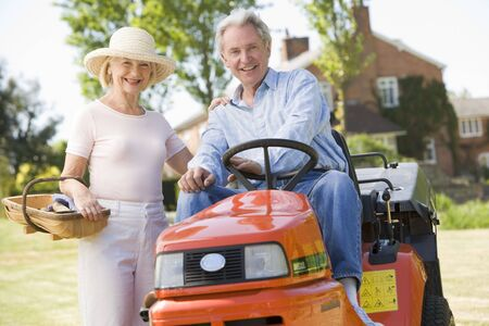 Couple outdoors with tools and lawnmower smiling photo