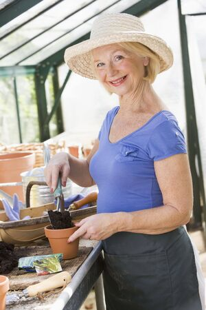 Woman in greenhouse putting soil in pot and smiling Stock Photo - 3474933