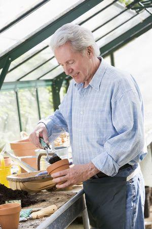 Man in greenhouse putting soil in pot smiling Stock Photo - 3475116