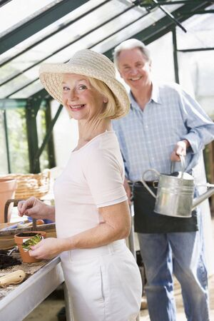 watering can: Woman in greenhouse planting seeds and man holding watering can smiling Stock Photo