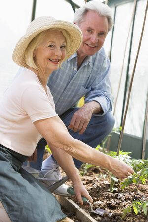 Woman in greenhouse planting seeds and man holding watering can smiling photo