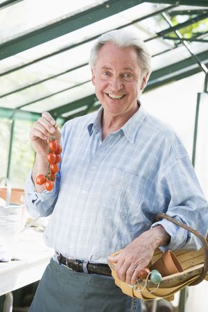 Man in greenhouse holding cherry tomatoes smiling photo
