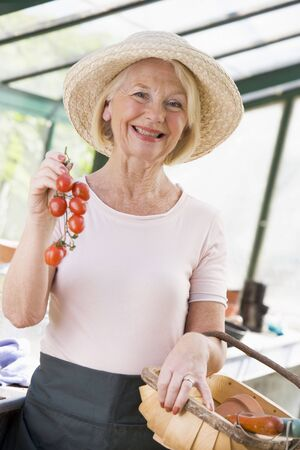 Woman in greenhouse holding cherry tomatoes smiling photo