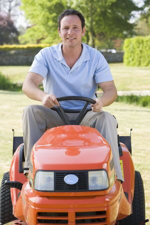 Man outdoors driving lawnmower smiling photo