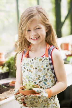 Young girl in greenhouse holding potted plant smiling photo