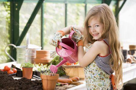 invernadero: Niña de riego en invernadero de plantas en maceta sonriente  Foto de archivo