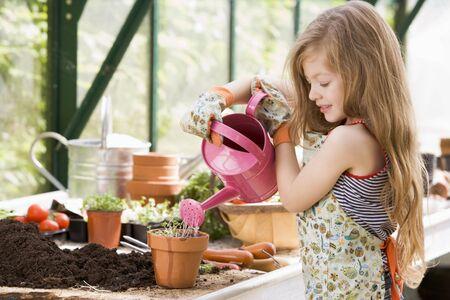 invernadero: Ni�a de riego en invernadero de plantas en maceta sonriente  Foto de archivo