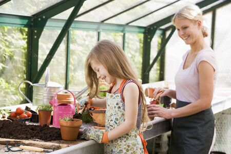 Young girl and woman in greenhouse putting soil in pots smiling Stock Photo - 3472735