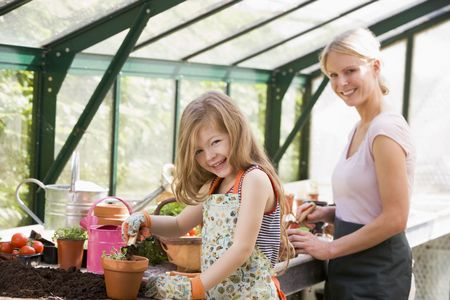 smiling woman in a greenhouse: Young girl and woman in greenhouse putting soil in pots smiling Stock Photo