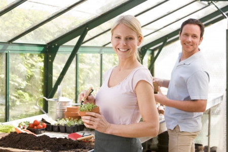 Couple in greenhouse raking soil in pots smiling photo