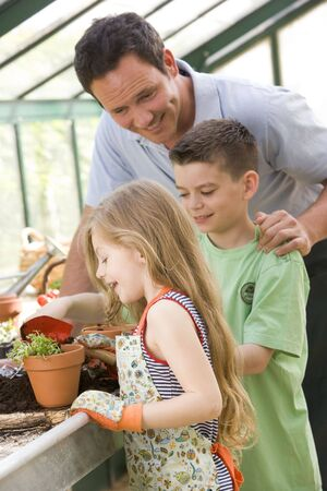 Man in greenhouse helping two young children putting soil in pot Stock Photo - 3475019