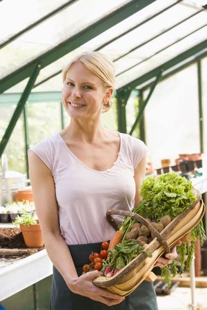 Woman in greenhouse holding basket of vegetables smiling photo