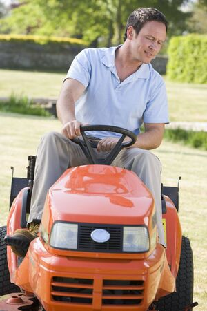 Man outdoors driving lawnmower photo