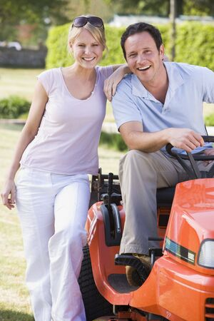 Couple outdoors with lawnmower smiling photo