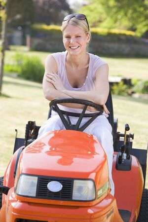 Woman outdoors with lawnmower smiling photo