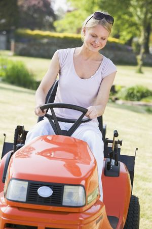 Woman outdoors driving lawnmower smiling Stock Photo