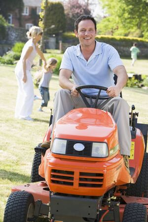 Man outdoors driving lawnmower smiling with  in background photo