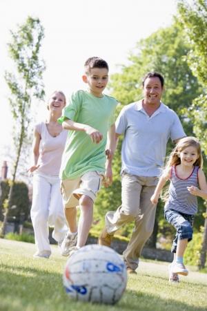ni�as jugando: La familia al aire libre, jugar al f�tbol y divertirse Foto de archivo