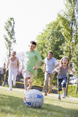 hermanos jugando: La familia al aire libre, jugar al f�tbol y divertirse Foto de archivo
