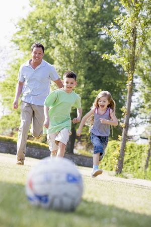 Man and two young children outdoors playing soccer and having fun photo