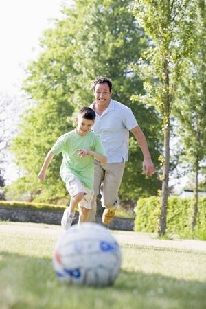 Man and young boy outdoors playing soccer and having fun photo
