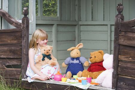 Young girl in shed playing tea and smiling photo
