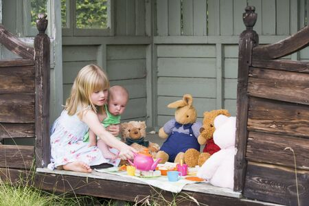 Young girl in shed with baby playing tea photo