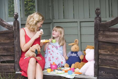 Woman and young girl in shed playing tea and smiling photo