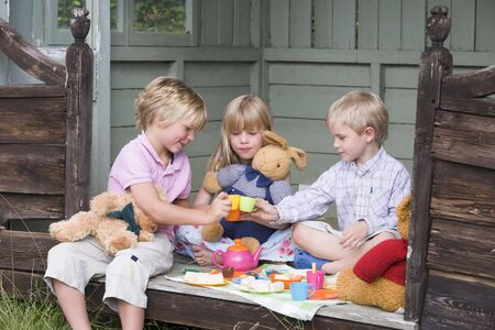 friends party: Three young children in shed playing tea and smiling Stock Photo