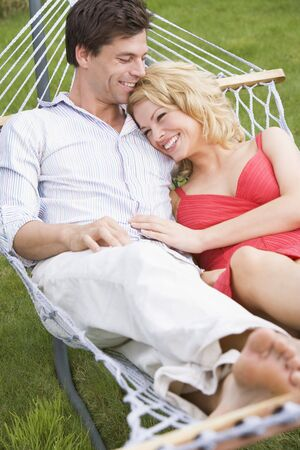 Couple relaxing in hammock smiling photo
