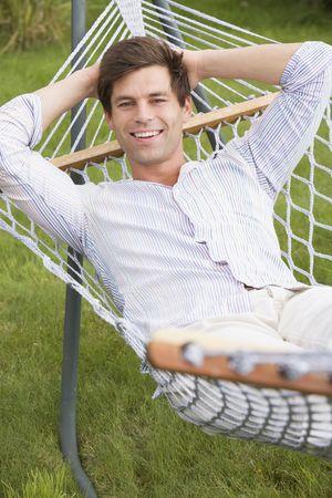 Man relaxing in hammock smiling photo