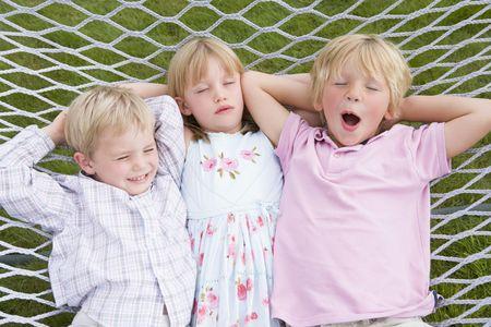 Three children relaxing and sleeping in hammock photo