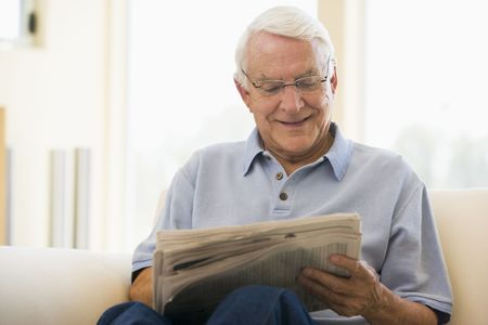 Man in living room reading newspaper smiling Stock Photo - 3458945