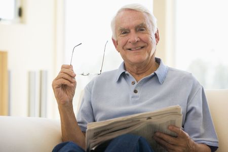 Man in living room reading newspaper smiling photo