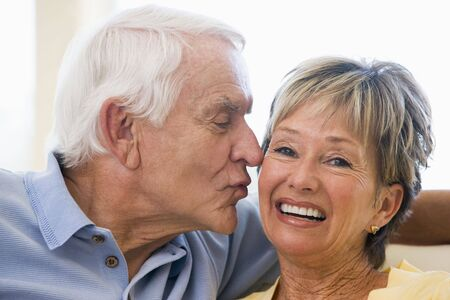 Couple relaxing in living room kissing and smiling Stock Photo - 3475203
