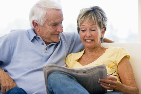 Couple in living room reading newspaper smiling photo