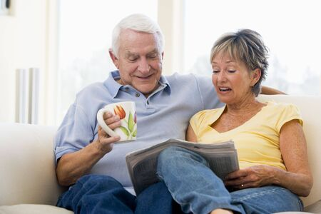 Couple in living room reading newspaper with coffee smiling photo