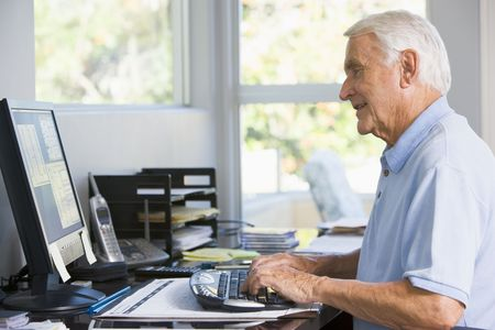 Man in home office using computer smiling Stock Photo - 3460909