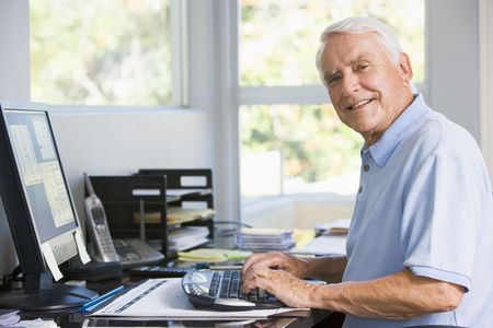 Man in home office using computer smiling Stock Photo - 3460945
