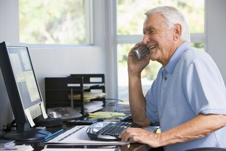 Man in home office on telephone using computer smiling Stock Photo - 3461057