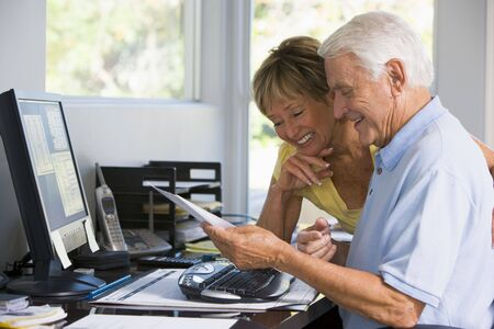 Couple in home office with computer and paperwork smiling photo