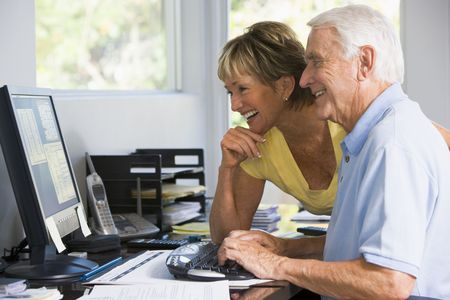 silver surfer: Couple in home office with computer and paperwork smiling