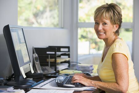 home office desk: Woman in home office using computer smiling Stock Photo
