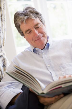 Man in living room reading book smiling photo