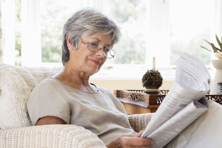 Woman in living room reading newspaper photo